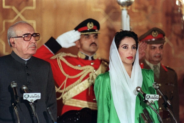 Benazir Bhutto (R) and President Ghulam Ishaq Khan, stand as the national anthem is being played before oath taking of Mrs Bhutto as first woman Prime minister of Pakistan ,December 1988.