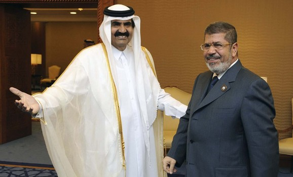 Qatar's Emir Sheikh Hamad bin Khalifa al-Thani (R) greets Egypt's President Mohamed Mursi during the Arab League summit in Doha March 26, 2013. Picture taken March 26, 2013.