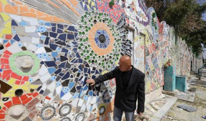 Syrian-artist-Moaffak-Makhoul-poses-near-his-decorated-wall-after-it-won-the-guinness-world-