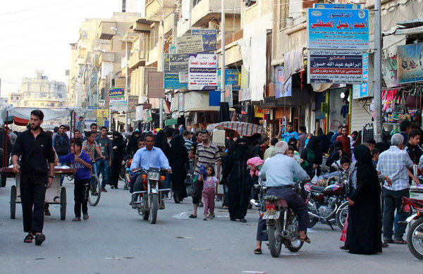 ISIS 15isiswomen-web5-articleLargeThe Tal Abyad street market last year, before the Eid al-Adha festival. Credit Reuters